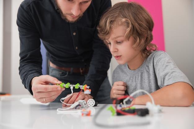 Mannelijke leraar attente schooljongen helpen om robot te maken tijdens technologieles op school Premium Foto