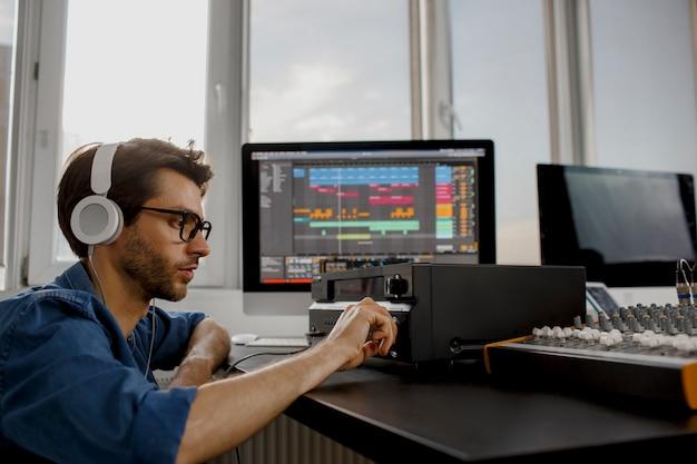 Mannelijke muziekarranger werkt met geluidsversterker Premium Foto