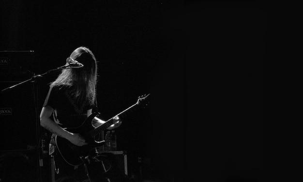 Mannelijke muzikant gitaar spelen op een podium in de buurt van de microfoon in zwart-wit Gratis Foto