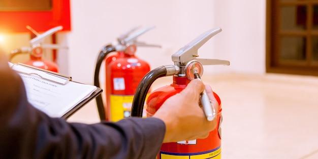 Mannelijke professionele inspectie brandblusser, veiligheidsconcept. Premium Foto