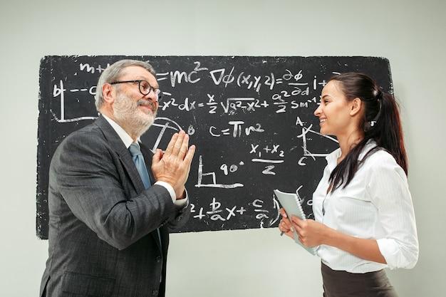 Mannelijke professor en jonge vrouw tegen schoolbord in de klas Gratis Foto