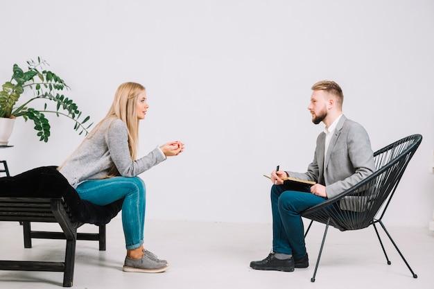 Mannelijke psycholoog die voor vrouwelijke patiënt zit die aan haar probleem luistert Gratis Foto