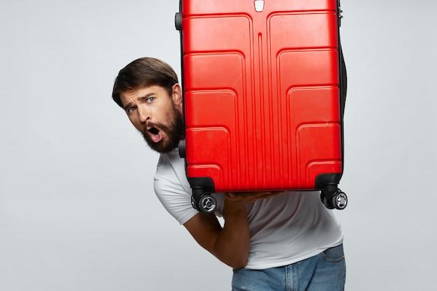 Mannelijke reiziger met een koffer in zijn handen die, vakantie stellen Premium Foto