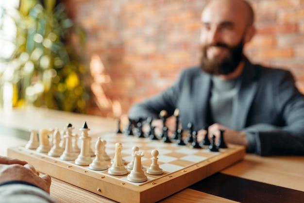 Mannelijke schakers beginnen te spelen, focus aan boord met figuren. Premium Foto