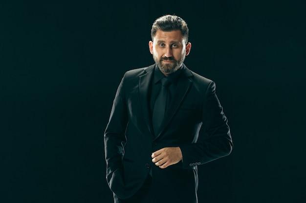 Mannelijke schoonheid concept. portret van een modieuze jonge man met een stijlvol kapsel, gekleed in trendy pak poseren Gratis Foto