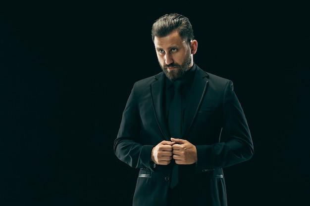 Mannelijke schoonheid concept. portret van een modieuze jonge man met een stijlvol kapsel trendy pak poseren op zwarte achtergrond. Gratis Foto