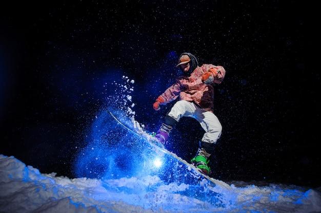 Mannelijke snowboarder gekleed in een witte en roze sportkleding voert trucs uit op de sneeuwhelling Premium Foto