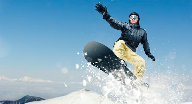 Mannelijke snowboarder, gevaarlijke bergaf in actie Premium Foto