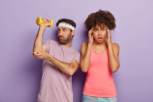 Mannelijke sportinstructeur oefent met halter, werkt aan het hebben van biceps, probeert zwaar voorwerp op te tillen, draagt hoofdband en t-shirt, vrouwelijke stagiair staat in de buurt, masseert tempels, moe na training Gratis Foto