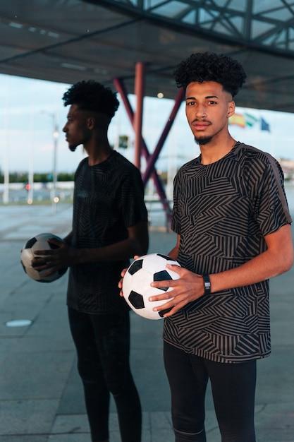 Mannelijke sportman die zich met voetbal op weerspiegelde achtergrond bevindt Gratis Foto