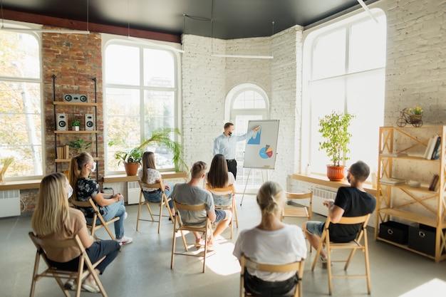 Mannelijke spreker geeft presentatie in hal op universitaire workshop. publiek of conferentiezaal Gratis Foto