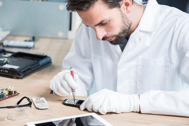 Mannelijke technicus die cellphone bevestigt Gratis Foto