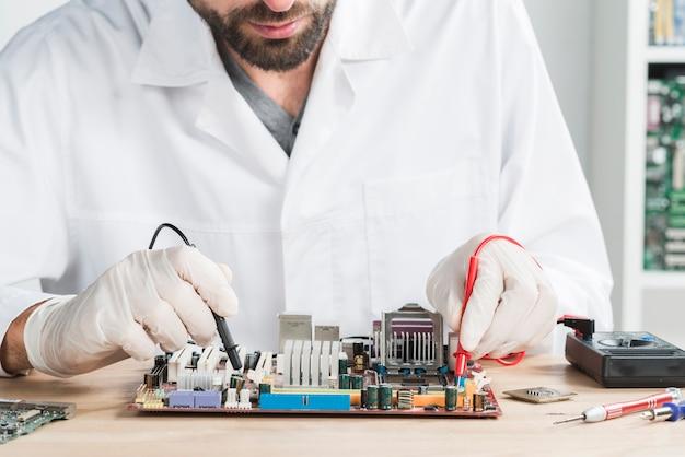 Mannelijke technicus die computer met digitale multimeter op houten bureau controleert Gratis Foto