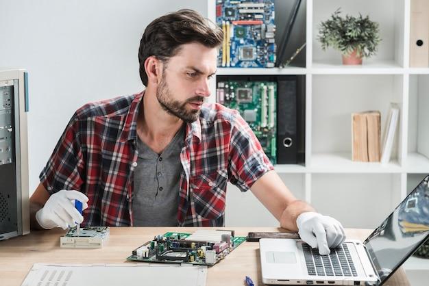 Mannelijke technicus die laptop bekijkt terwijl het herstellen van computer Gratis Foto