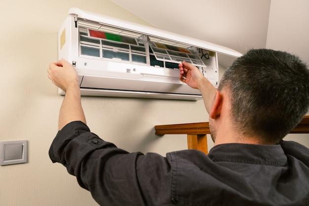 Mannelijke technicus schoonmakende airconditioner binnen Premium Foto