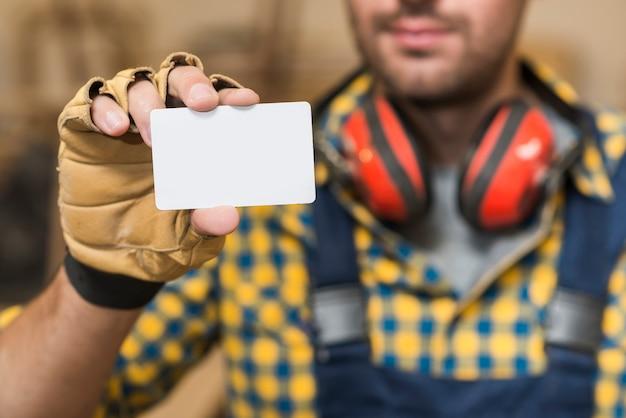 Mannelijke timmerman die leeg wit visitekaartje toont Gratis Foto