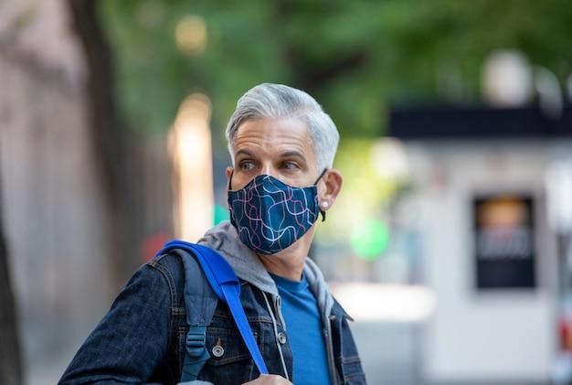 Mannelijke toerist in masker en met rugzak wandelen langs straat in madrid en genieten van uitzicht op de stad Premium Foto