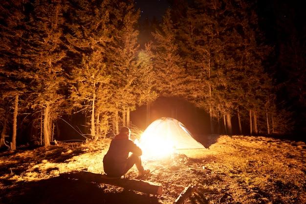 Mannelijke toerist rust 's nachts uit in zijn kamp bij het kampvuur en de tent onder een prachtige nachthemel vol sterren en de maan en geniet van een nachtscène in de bergen Premium Foto