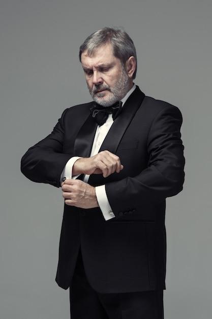 Mannelijke volwassene van middelbare leeftijd het dragen van een pak geïsoleerd op grijs Gratis Foto