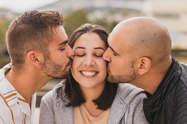 Mannelijke vrienden die vrouw kussen Gratis Foto