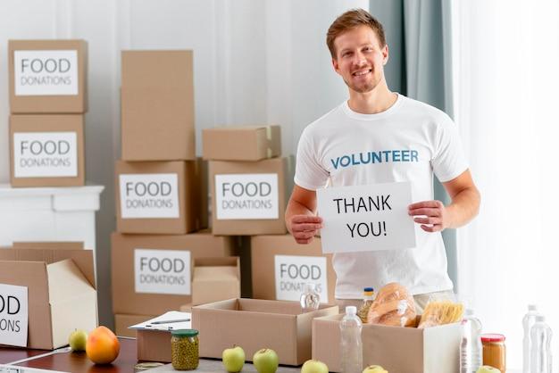 Mannelijke vrijwilliger die je bedankt voor het doneren van voedsel voor een goed doel Gratis Foto