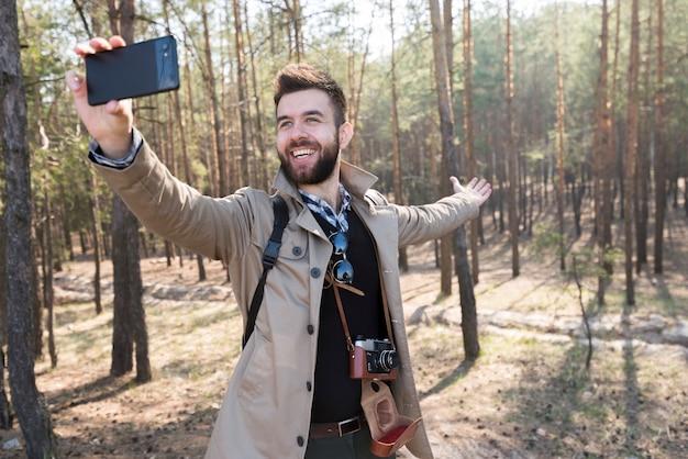 Mannelijke wandelaar die selfie op mobiele telefoon in het bos nemen Gratis Foto