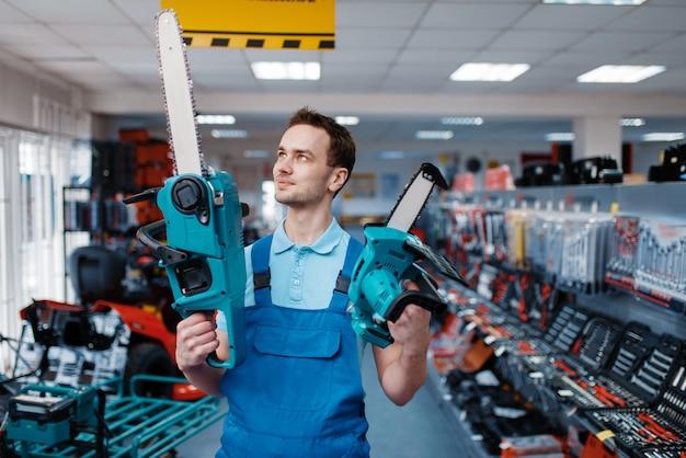Mannelijke werknemer in uniform houdt grote en kleine kettingzagen in gereedschapsopslag. keuze uit professionele apparatuur in ijzerhandel, instrumentensupermarkt Premium Foto