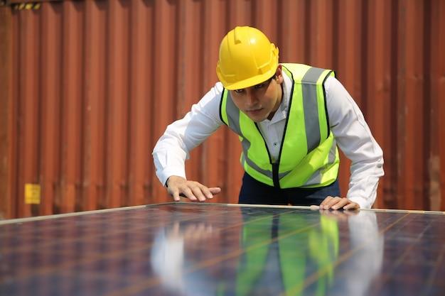 Mannelijke werknemer installeert zonnepaneel, technicus installeert zonnepanelen op dak. alternatieve energie zonne-energie, ecologisch concept. Premium Foto