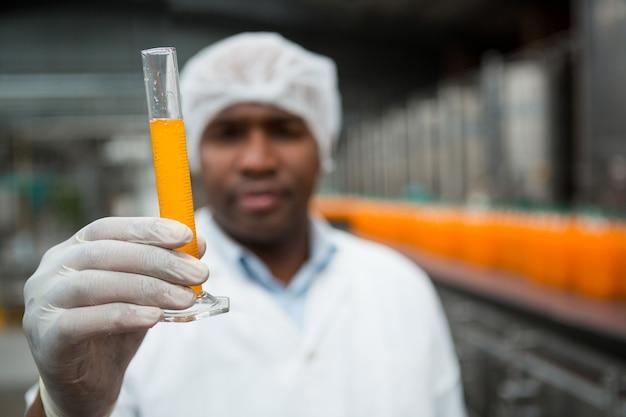 Mannelijke werknemer sap in fabriek controleren Gratis Foto