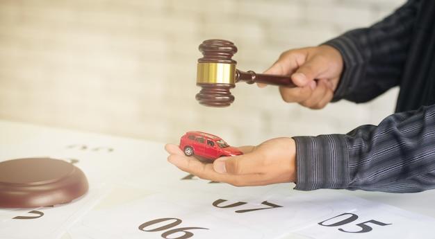 Mannelijke zakenman die een autoveiling modelhamer houdt Premium Foto