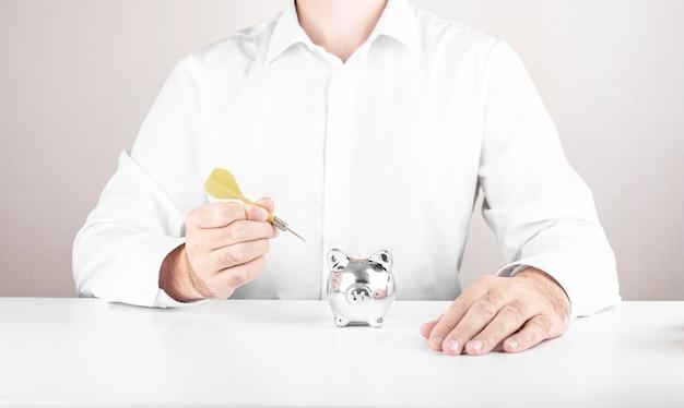 Mannelijke zakenman raakt het doelwit met darts. dobbelstenen aspiratie concept met spaarpot Premium Foto