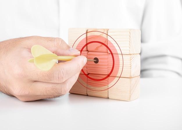 Mannelijke zakenman raakt het doelwit met darts. dobbelstenen aspiratie concept met welpen Premium Foto