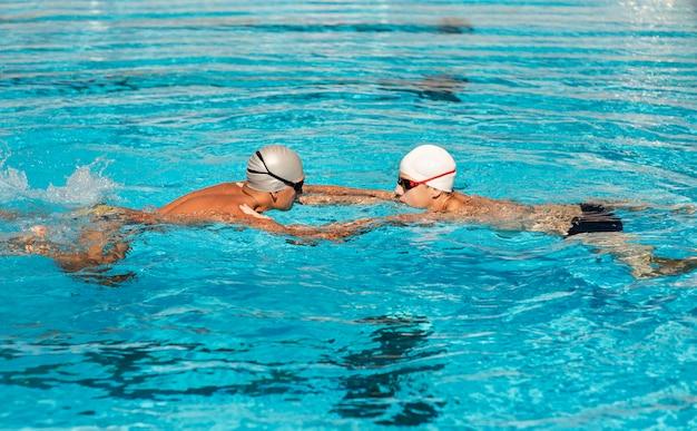 Mannelijke zwemmers die in het zwembad zwemmen Gratis Foto