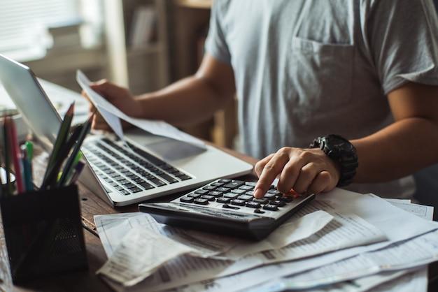 Mannen berekent de kosten van de rekening. ze drukt op de rekenmachine. Premium Foto