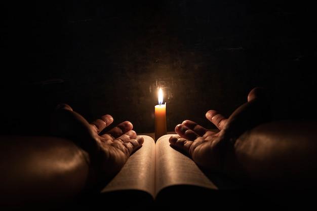 Mannen die op de bijbel in de lichte kaarsen selectieve nadruk bidden. Gratis Foto