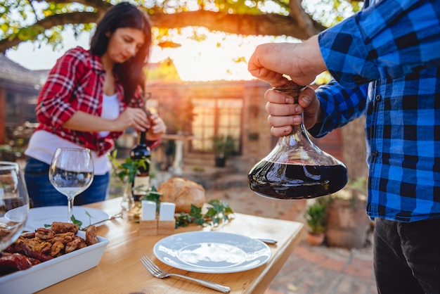 Mannen die wijnkaraf boven eettafel houden Premium Foto