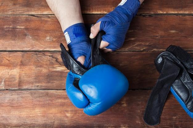 Mannen dienen boksbandages en bokshandschoenen in op een houten ondergrond. conceptvoorbereiding voor bokstraining of gevechten. plat lag, bovenaanzicht Premium Foto