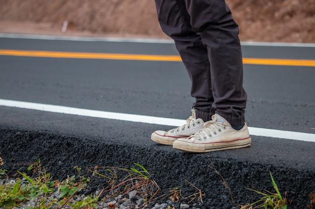 Mannen dragen sneakers op straat lopen met gele lijnen. Premium Foto