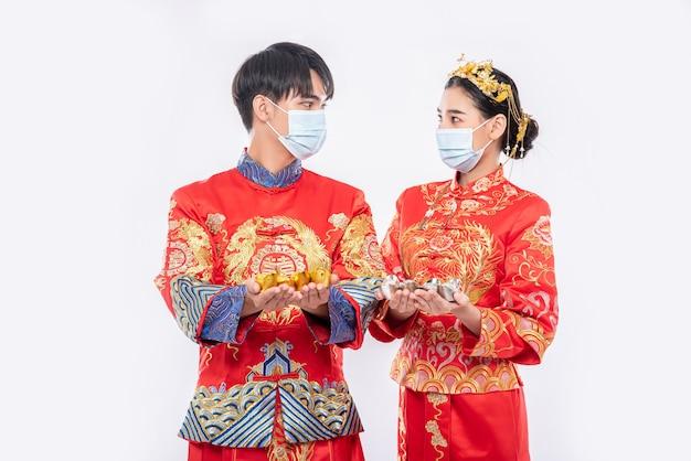 Mannen en vrouwen die qipao dragen en maskers dragen besteden met goudgeld Gratis Foto