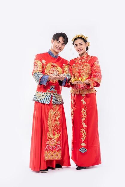 Mannen en vrouwen die qipao dragen, geven goudgeld uit Gratis Foto