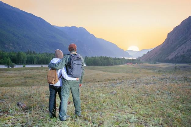 Mannen en vrouwen die rugzakken dragen die van zonsondergang genieten tijdens stijging op berg Premium Foto