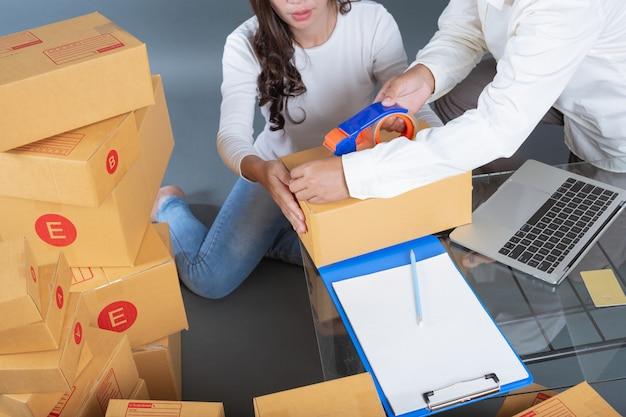 Mannen en vrouwen helpen de dozen in te pakken. Gratis Foto