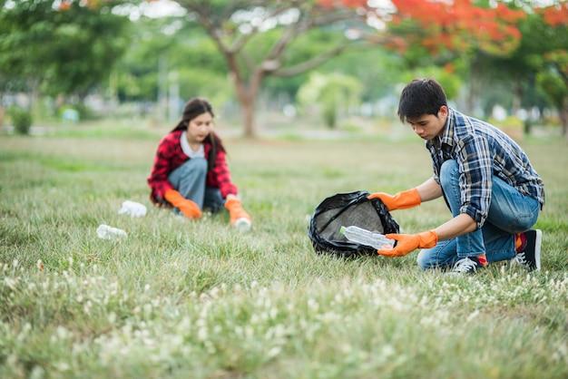 Mannen en vrouwen helpen elkaar bij het ophalen van afval. Gratis Foto