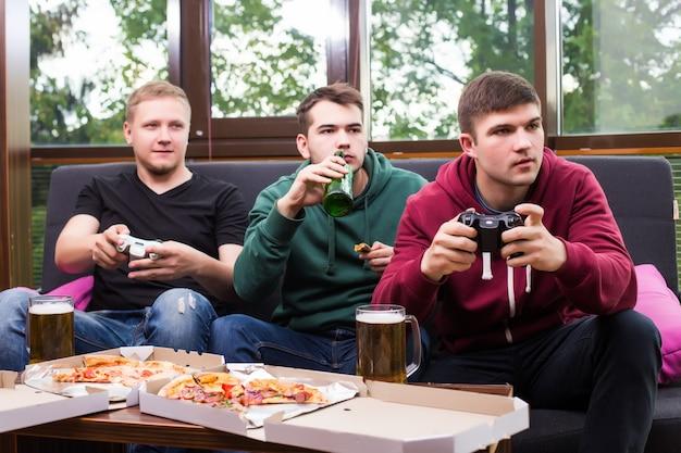 Mannen fans voetbal kijken op tv en bier drinken. drie mannen die bier drinken en samen plezier maken in de bar Gratis Foto