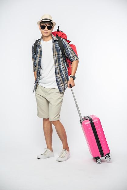 Mannen gekleed om te reizen, met bril en hoed, met tassen en bagage Gratis Foto