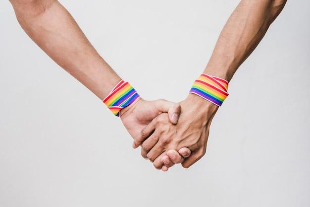Mannen houden handen met bands in lgbt-kleuren Gratis Foto