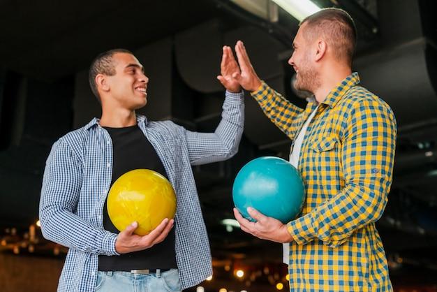 Mannen houden van kleurrijke bowlingballen Gratis Foto