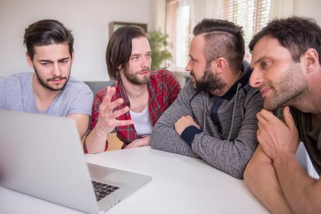 Mannen kijken naar video op een laptop Gratis Foto