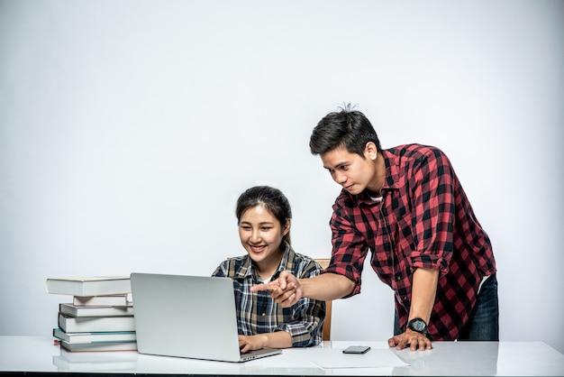 Mannen leren vrouwen op het werk met laptops te werken. Gratis Foto