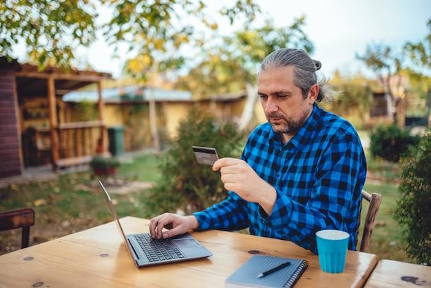 Mannen met creditcard op achtertuin patio Premium Foto